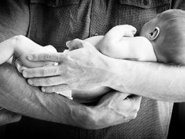 Cute newborn baby boy being held