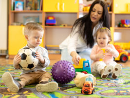 Nursery teacher looking after children in kindergarten. Little kids toddlers play together with developmental toys.