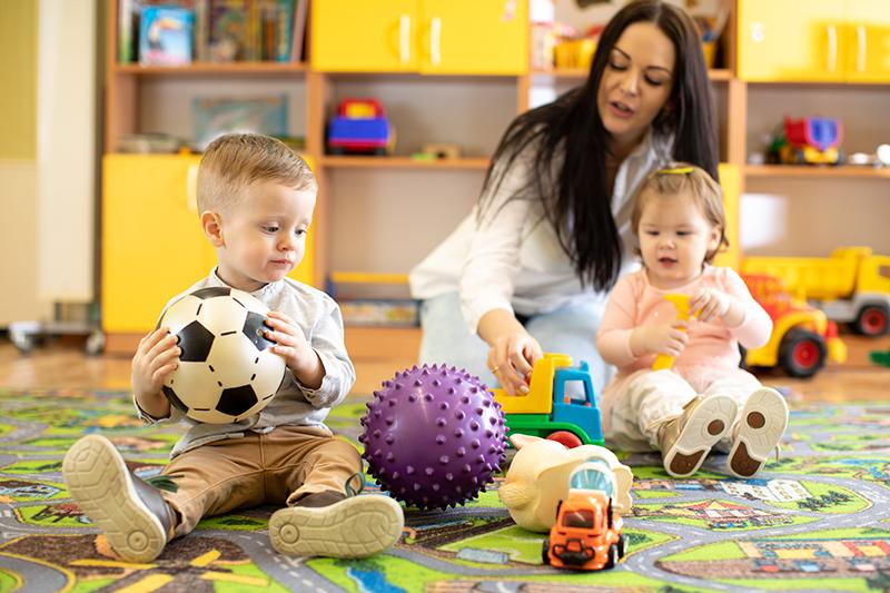 Nursery teacher looking after children in kindergarten. Little kids toddlers play together with developmental toys.