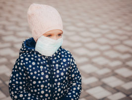 Little girl in protection mask outdoors. child plays in the street