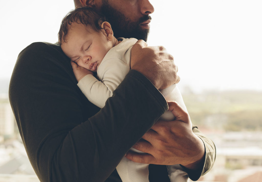 Man carrying his sleeping son. Newborn baby boy in his father's arms.